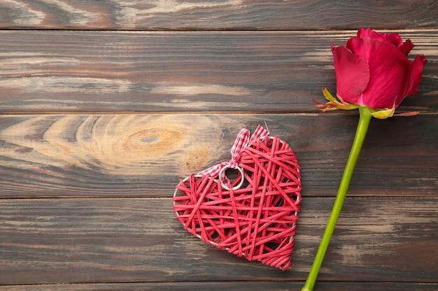 Rote rose und herz auf braunem hintergrund, valentinstagskonzept, liebessymbol. draufsicht
