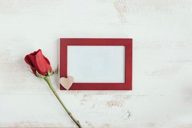 Rote rose und holzherz mit rahmen