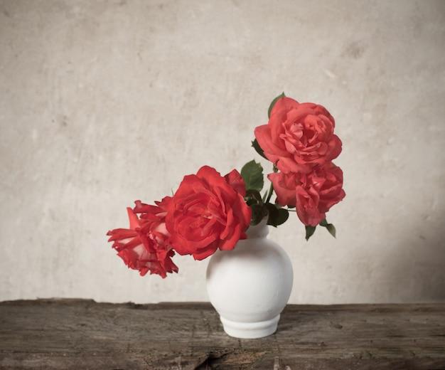 Rote rosen auf altem holztisch