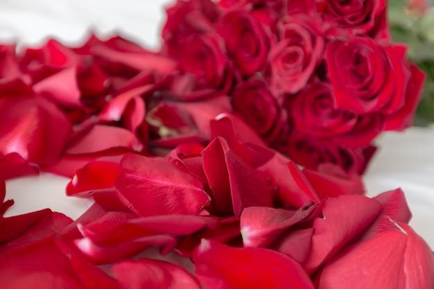 Rote rosen auf einem bett