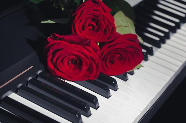 Rote rosen auf klaviertasten