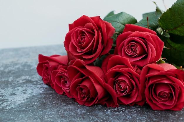 Rote rosen auf konkretem hintergrund