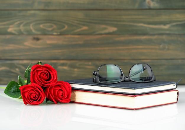 Rote rosen auf tisch und buch mit kopienraum, valentinstaghintergrund mit roten rosen
