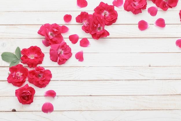 Rote rosen auf weißem holz