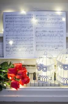 Rote Rosen auf weißem Klavier mit Noten, Girlanden und dekorativen Zellen