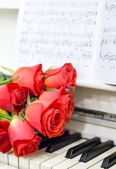 Rote rosen auf weißem klavier mit noten und girlanden
