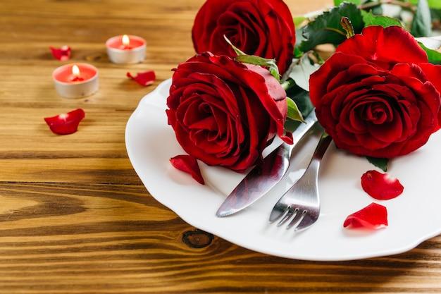 Rote rosen auf weißer platte