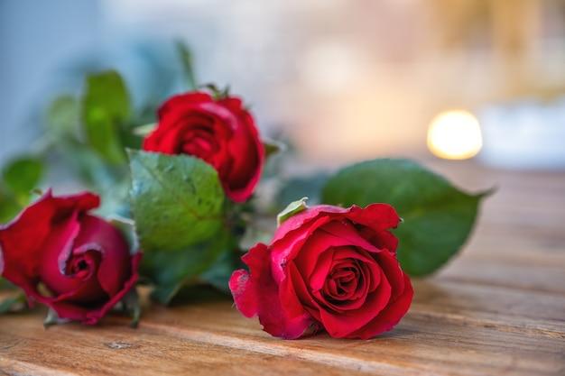 Rote rosen blühen auf holztisch mit unschärfehintergrund
