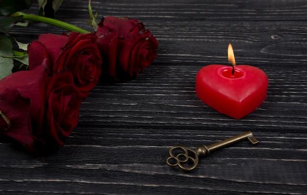 Rote rosen, eine herzförmige kerze und ein schlüssel
