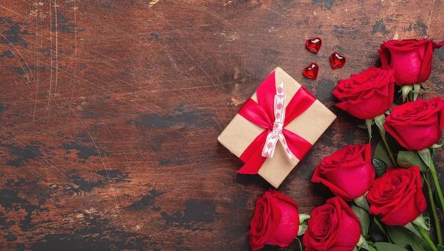 Rote rosen, geschenkbox und dekorative herzen auf holztisch.