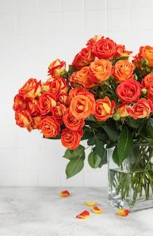 Rote rosen in einer glasvase auf dem tisch
