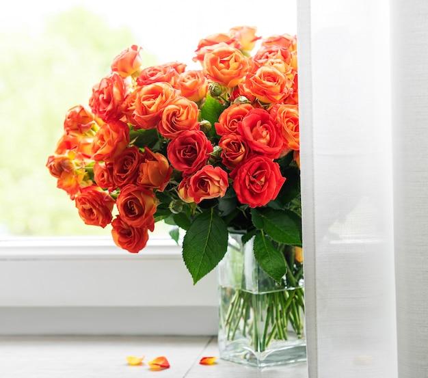 Rote rosen in einer glasvase auf der fensterbank