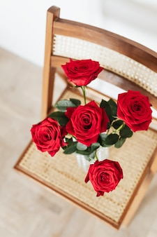 Rote rosen in einer glasvase auf einem holzstuhl