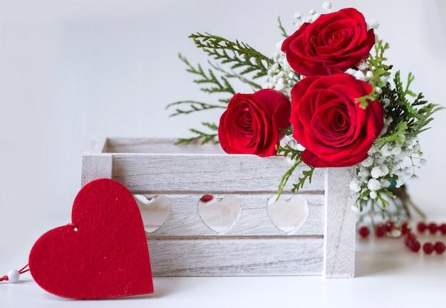 Rote rosen in einer holzkiste mit einem filzherzen