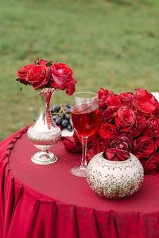 Rote rosen in einer vase und auf dem tisch und ein glas rotwein auf dem tisch, romantisches dekor