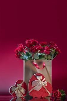 Rote rosen in großer basteltasche herzförmige geschenkbox rosenperlen auf einer spiegelfläche