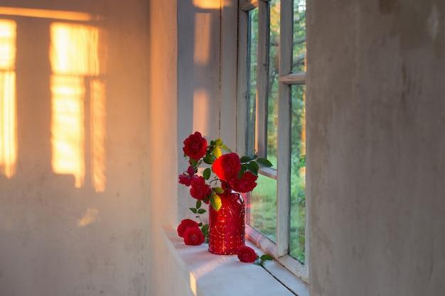 Rote rosen in roter glasvase auf fensterbank