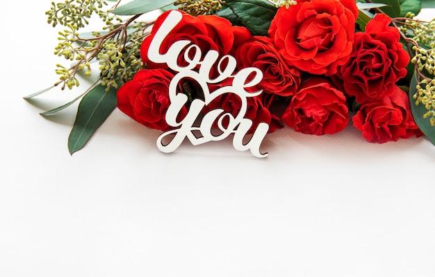 Rote rosen mit eukalyptus verzweigen sich mit liebe sie aufschrift