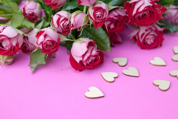 Rote rosen mit hölzernen herzen auf einem rosa hintergrund