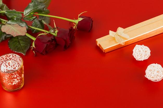 Rote rosen mit kerze auf dem tisch
