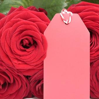 Rote rosen mit leerem tag für valentinstagzeichen