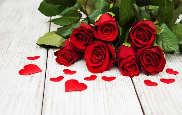Rote rosen mit seidenherzen