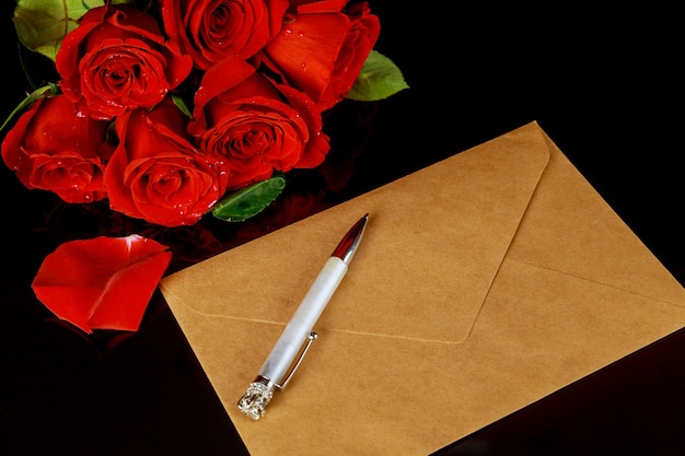 Rote rosen mit umschlag und stift auf schwarzem tisch. valentinstag konzept.