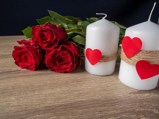 Rote rosen neben weißen kerzen und roten herzen auf dem tisch