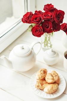 Rote rosen, tee und hörnchen auf einem tisch nahe dem fenster, romantisches frühstück für valentinstag