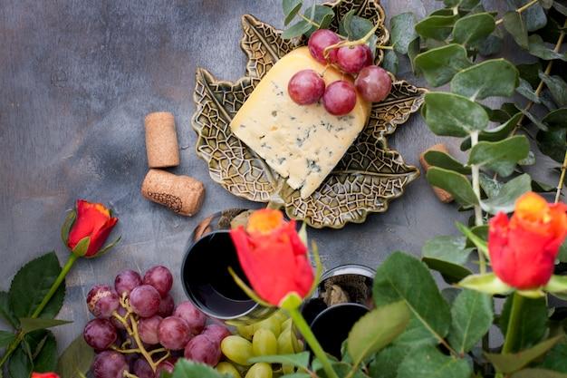Rote rosen, trauben, käse und ein glas rotwein auf einem grauen konkreten hintergrund