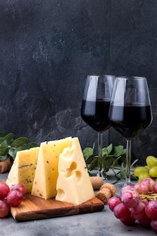 Rote rosen, trauben, käse und ein glas rotwein auf einem schwarzen konkreten hintergrund
