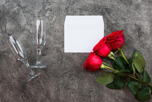 Rote rosen, umschlag und gläser