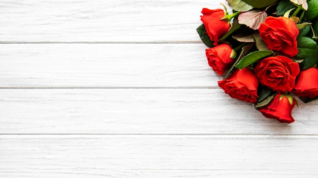 Rote rosen und blumenblätter auf weißem hölzernem hintergrund