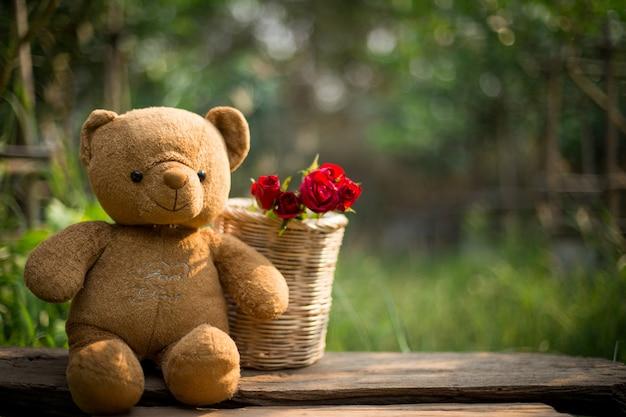 Rote rosen und ein teddybär betreffen hölzernen hintergrund