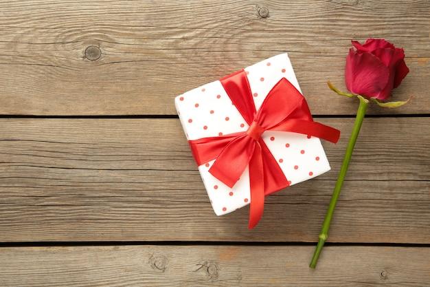 Rote rosen und geschenkbox auf einem hölzernen hintergrund. valentinstag