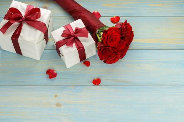 Rote rosen und geschenkbox auf hellblauem holztisch, oberseite angesehen