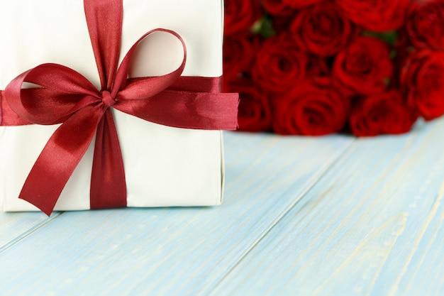 Rote rosen und geschenkbox auf hellblauem holztisch.