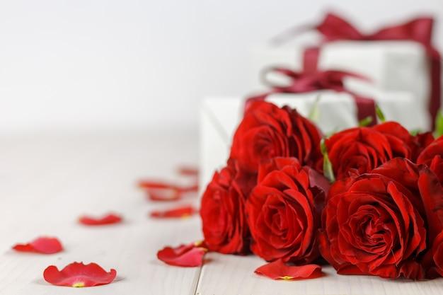 Rote rosen und geschenkbox auf weißem holztisch