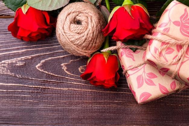 Rote rosen und geschenkbox. blumen in der nähe von garnballen. kunst, geschenke zu machen. schönheit des handwerks.