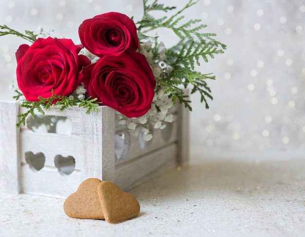 Rote rosen und herzen mit einem glänzenden hintergrund