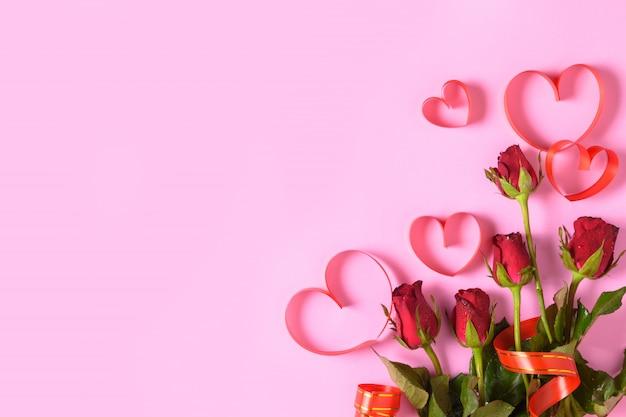 Rote rosen und herzrotes band auf rosa hintergrund,