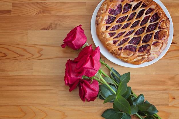 Rote rosen und kirschtorte auf einem holztisch