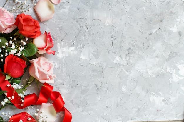 Rote rosen und kleine weiße blumen mit band auf grauem hintergrund