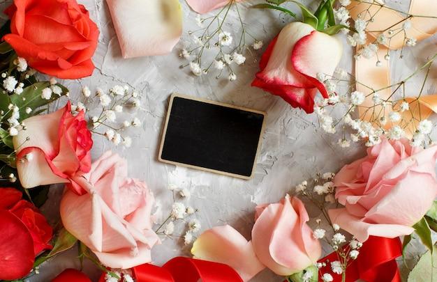 Rote rosen und kleine weiße blumen mit einer tafel auf einem grauen hintergrund