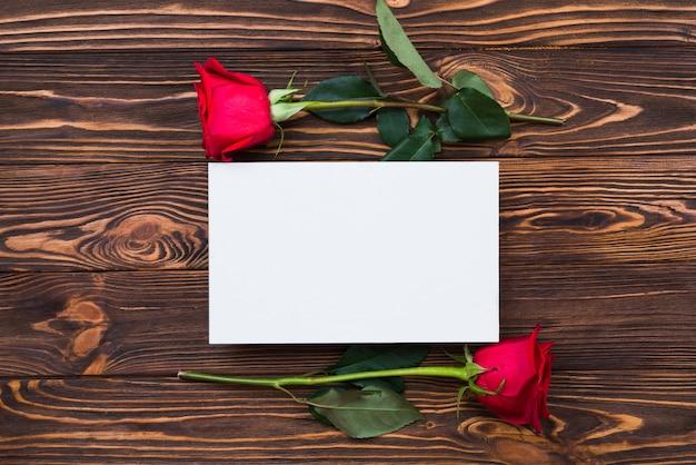 Rote rosen und leeres blatt papier auf hölzernem brett