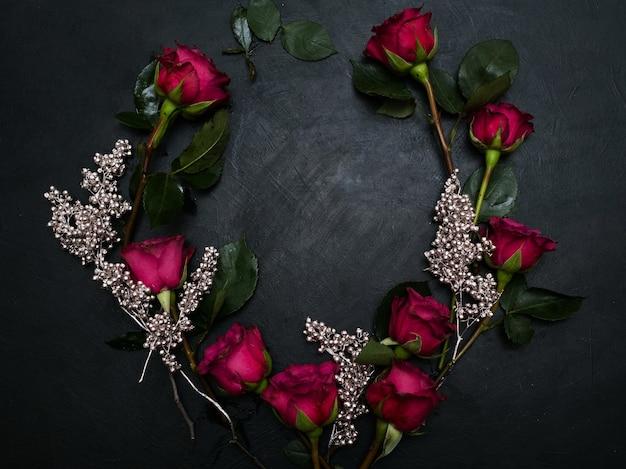Rote rosen und silberdekor mischen sich auf dunklem hintergrund. schönes blumenkranzdesign. liebe und schönheit. negativraumkonzept