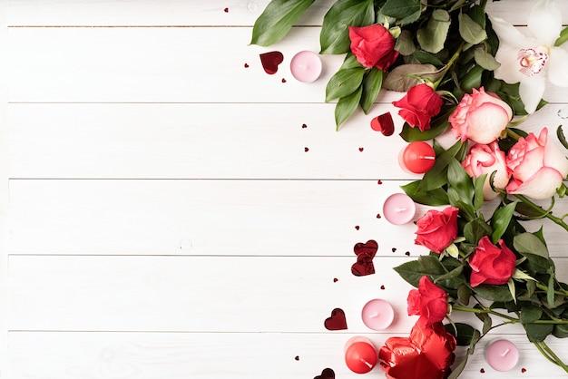 Rote rosen und valentinstagdekorationen draufsicht auf weißem hölzernem hintergrund