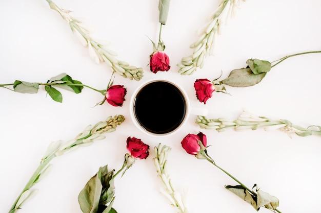 Rote rosen und weiße blumen rahmen mit kaffeetasse auf weißer oberfläche ein