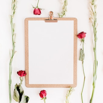 Rote rosen und weißer blumenrahmen mit zwischenablage