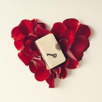 Rote rosenblätter in einer herzform mit buch auf weißer wand. flach liegen